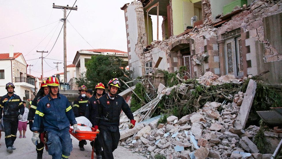 Bomberos sacando el cuerpo de una persona de entre los escombros.
