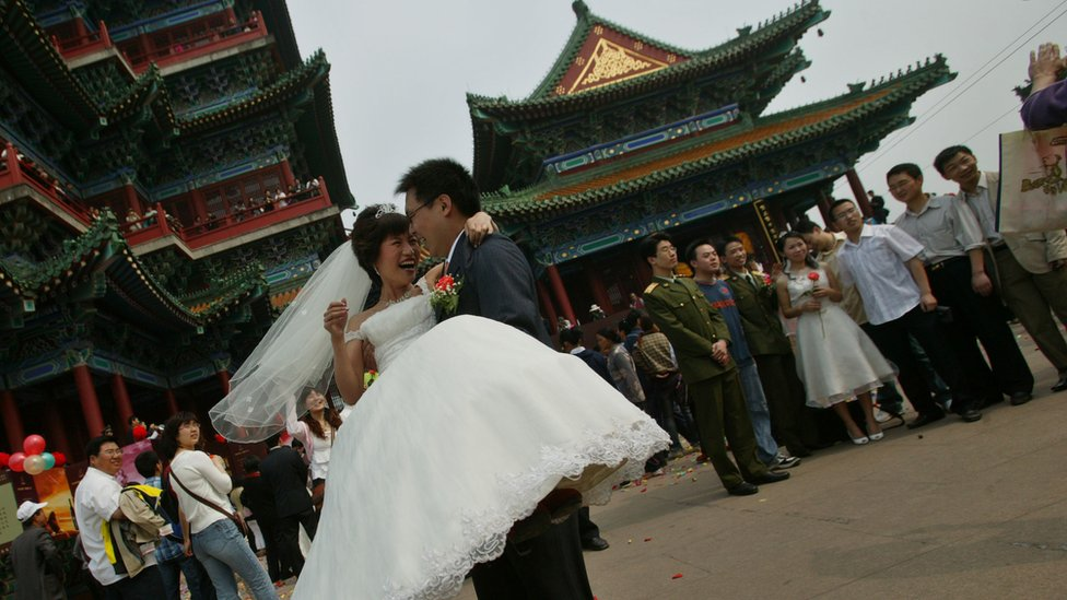 A Chinese groom lifts up his bride