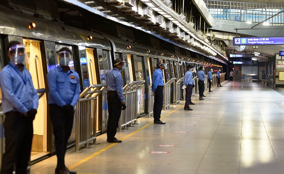 Security guards wearing face shields seen beside a train at Rajiv Chowk Metro Station during a press preview of Delhi Metro Rail Corporation (DMRC) preparedness ahead of metro services resuming on September 3, 2020
