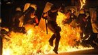 Riot police officers run through fire as anti-austerity protesters throw petrol bombs, during clashes in Athens