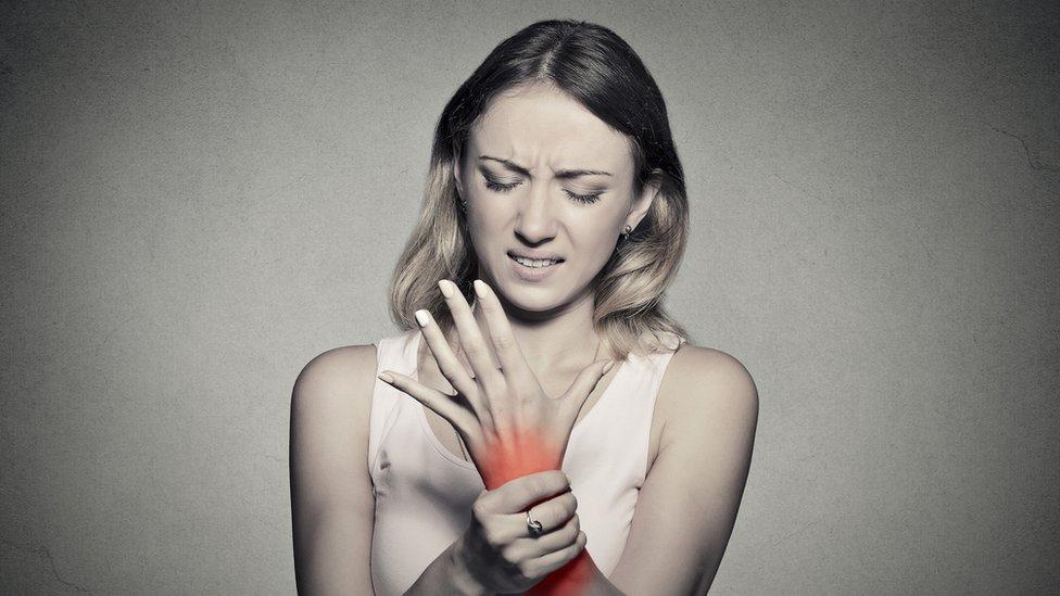 Mujer sintiendo dolor en una mano.