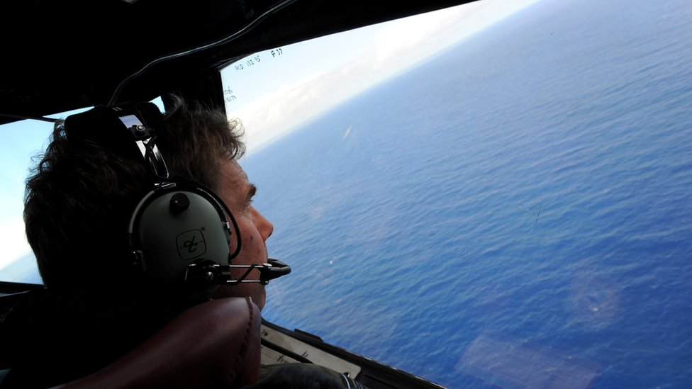 Co-pilot and Squadron Leader Brett McKenzie of the Royal New Zealand Airforce (RNZAF) P-3K2-Orion aircraft, helps to look for objects during the search for missing Malaysia Airlines flight MH370