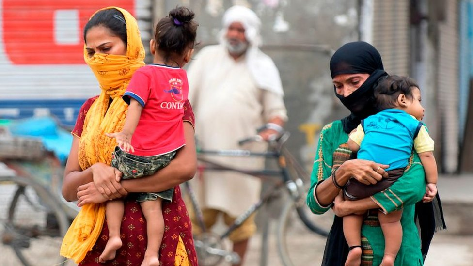Las mujeres con máscaras llevan a sus hijos y caminan por las afueras de Amritsar el 5 de septiembre de 2020.