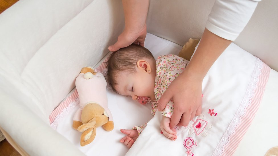 Manos de una mujer colocan a un bebé en su cuna