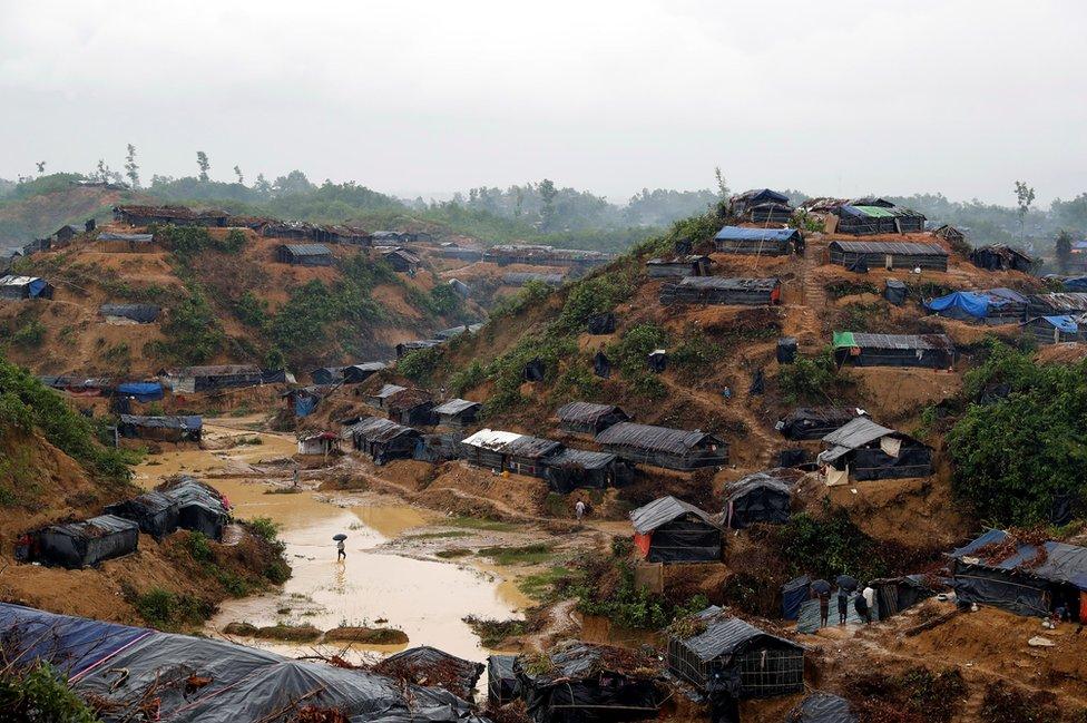 Vista de un campo de refugiados con muchas casas improvisadas de bambú y lonas. Está inundado por las lluvias.