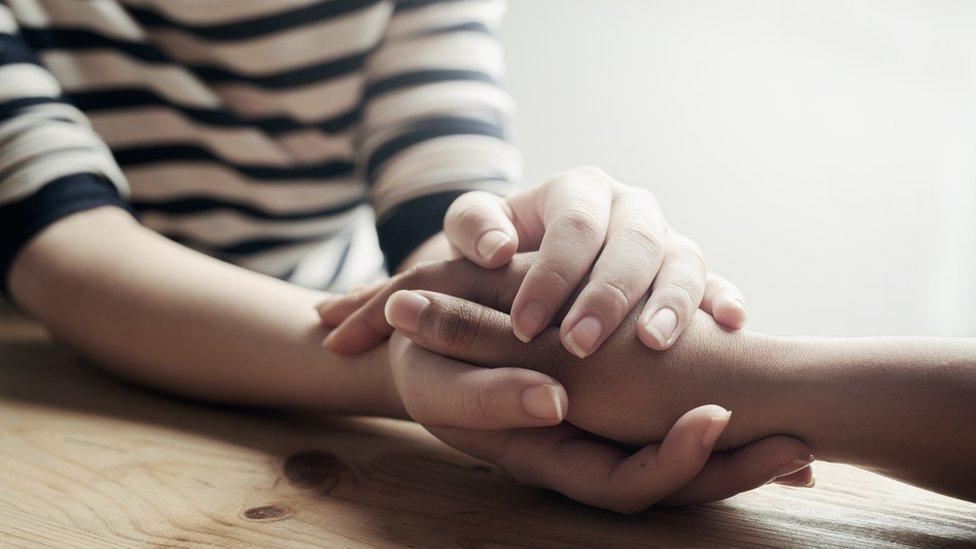 Dos personas agarradas de la mano.