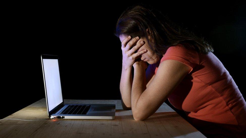 niña usando computadora y cubriéndose la cara.
