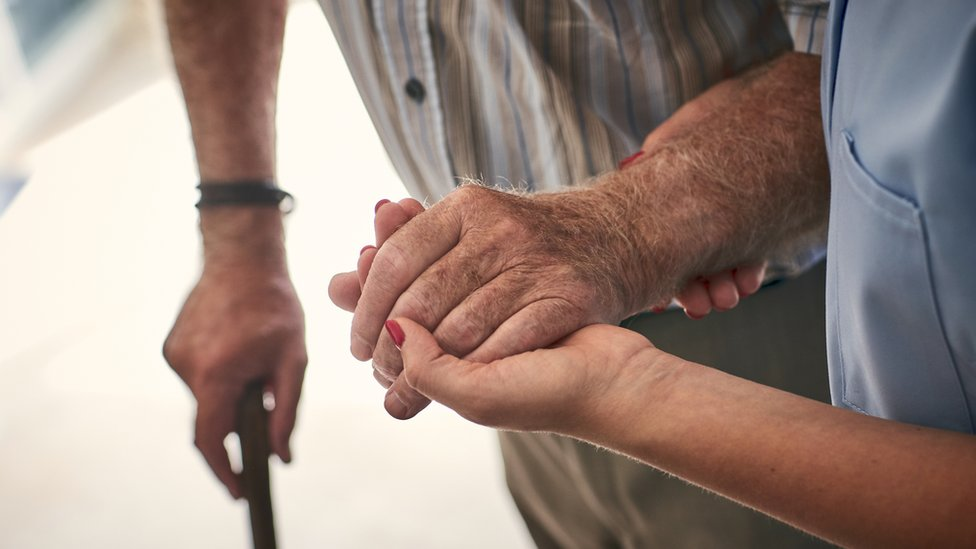 شخص يساعد رجلا مسنا