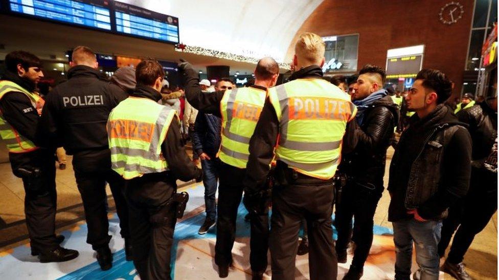 رجال شرطة يتحققون من وثائق عدد من الأشخاص في محطة القطارات الرئيسية في كولونيا