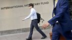 People walk past the headquarters of the International Monetary Fund on 30 June 2015 in Washington, DC.