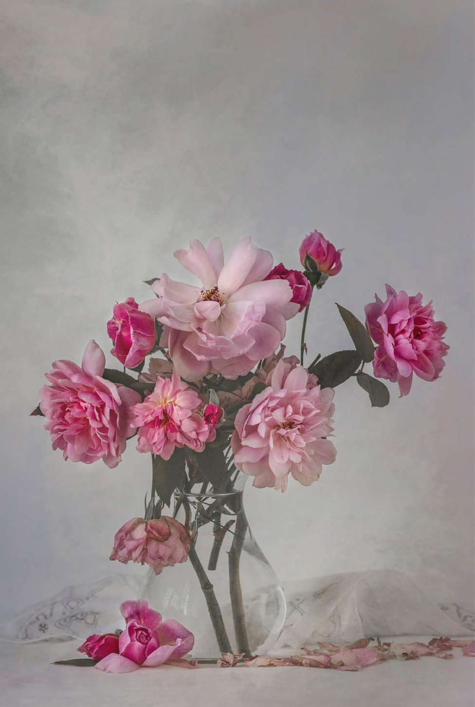 Fading pink roses in a vase with linen napkins on the table