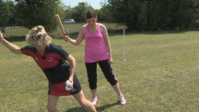 trainer showing a woman the correct stance for batting in rounders