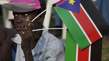 A man holds the flag of South Sudan