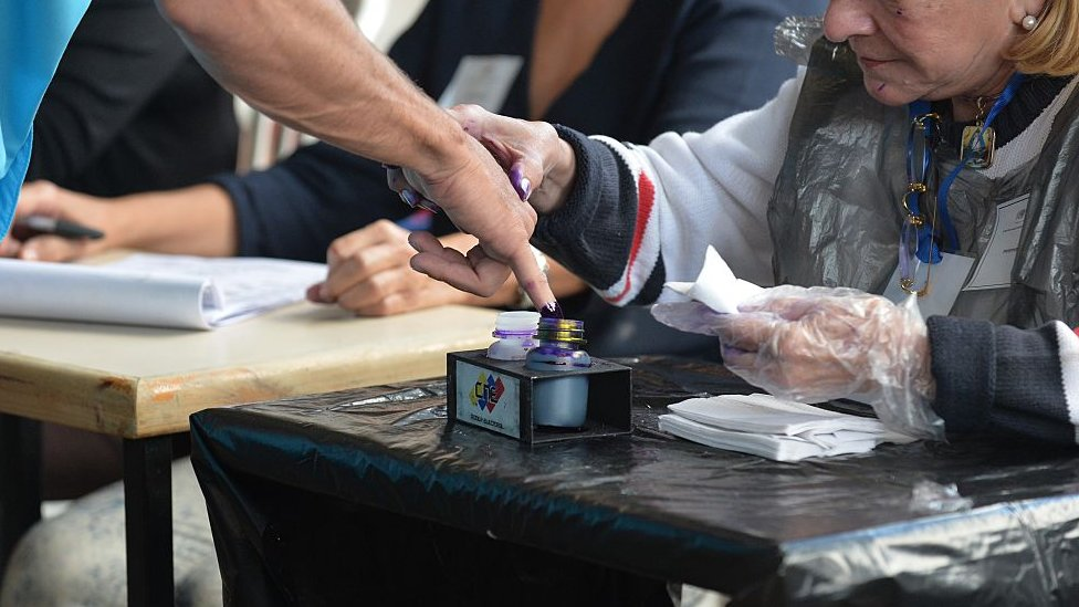Un votante moja su dedo con tinta indeleble.