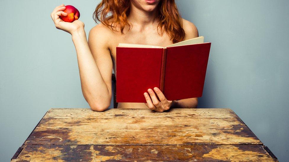 Mujer sin camisa leyendo un libro