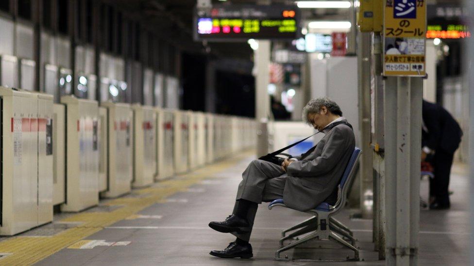 Un hombre dormido en una estación de metro de Tokyo.