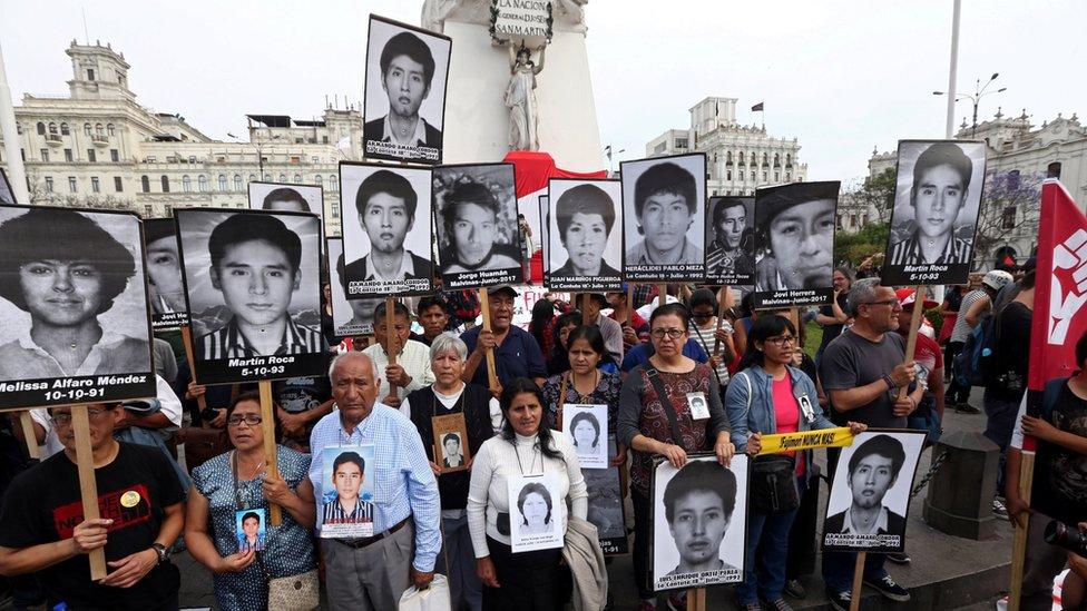 Manifestantes con imágenes de las víctimas de las matanzas de Barrios Altos y La Cantuta.