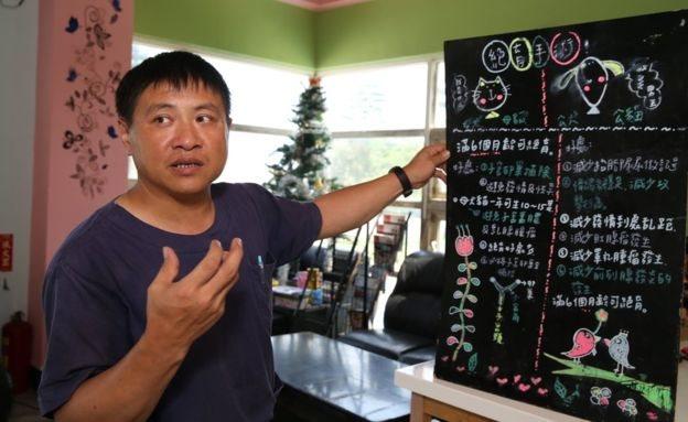 Un hombre explica algo en una cartelera