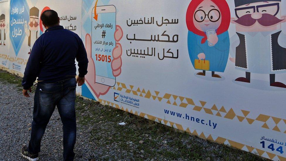 رجل يقف أمام ملصق دعائي للانتخابات
