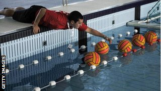 Volunteer arranging water polo balls after training session