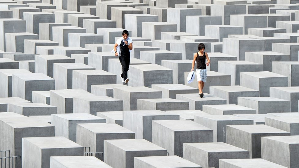 Dos visitantes caminan sobre los pilares del monumento al holocausto en Berlín. Foto de 2010.