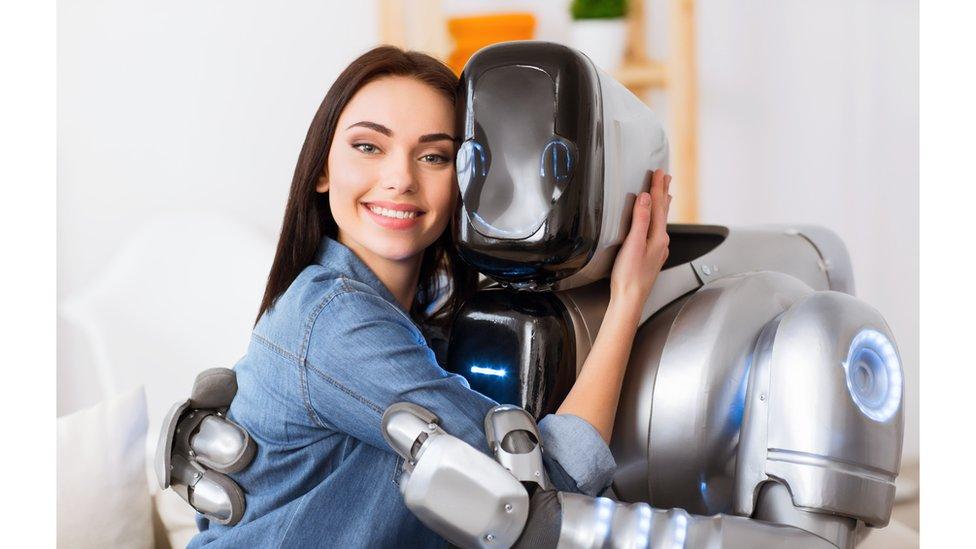 Una mujer abrazando un robot