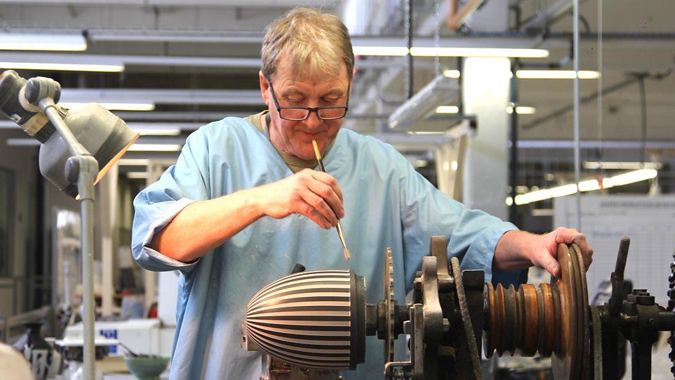Neil Burton ha trabajado como tornador en Wedgwood por 44 años. Aquí está aplicándole adhesivo a la base del jarrón para pegarle el cuello.