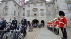 A guard of honour saluting WW2 veterans in wheelchairs as they being pushed by relatives and friends through Horse Guards Parade