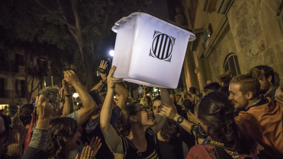 An election official carries an empty polling box out of the polling station after the counting had finished for the referendum vote on October 1, 2017 in Barcelona