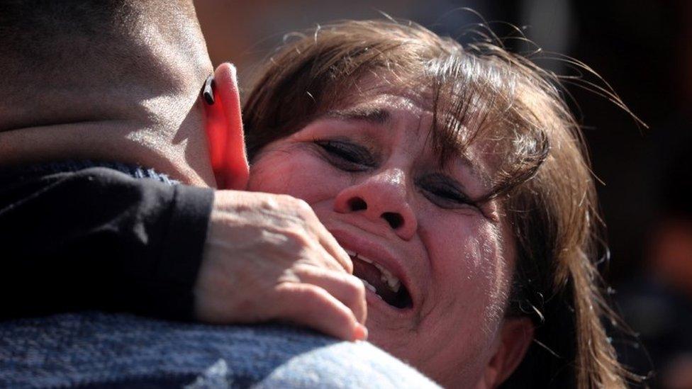 Una mujer abraza a un hombre en la apertura de la frontera