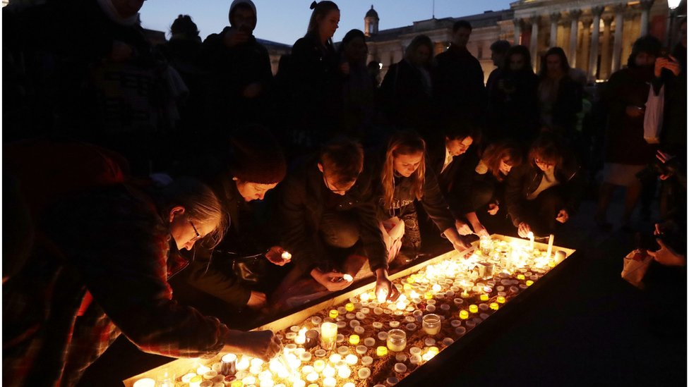 Grupo de personas encendiendo velas en Trafalgar Square.