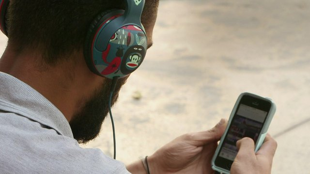 Man listening to music on phone with bright headphones