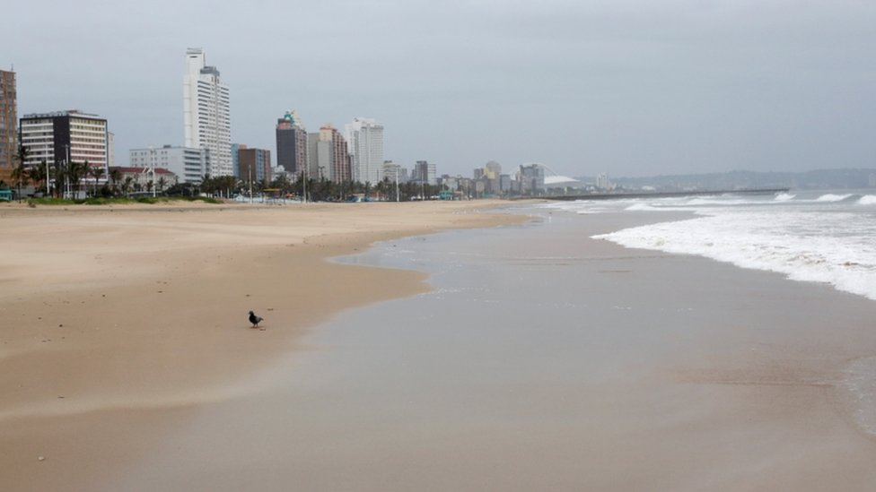 General view of an empty beach with high-rise buildings in the distance.