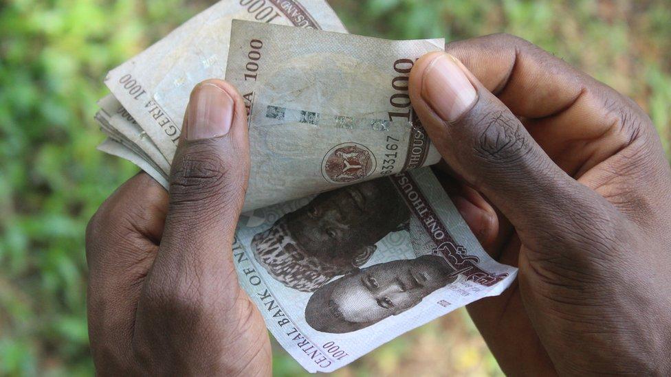 Someone counting 1,000 naira notes