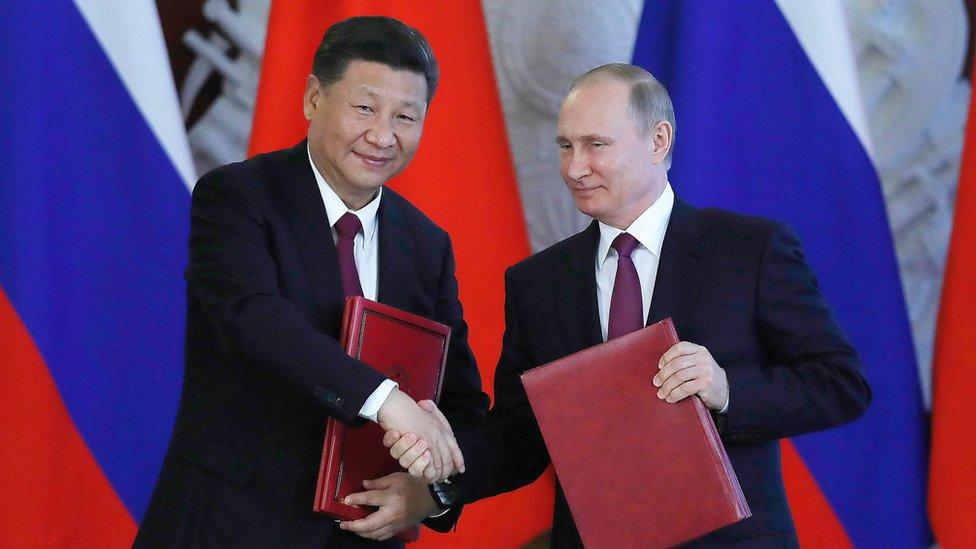 Vladimir Putin y Xi Jinping dándose la mano.