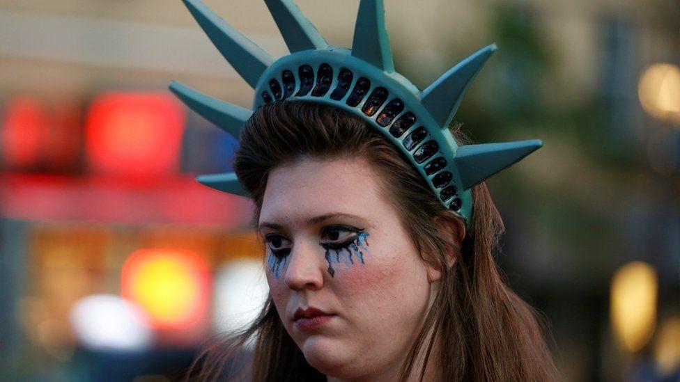 متظاهرة وضعت تاج تمثال الحرية على رأسها وهي تبكي
