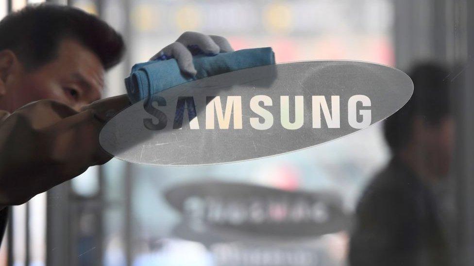 un hombre limpia el logo de Samsung en el escaparate de una tienda.
