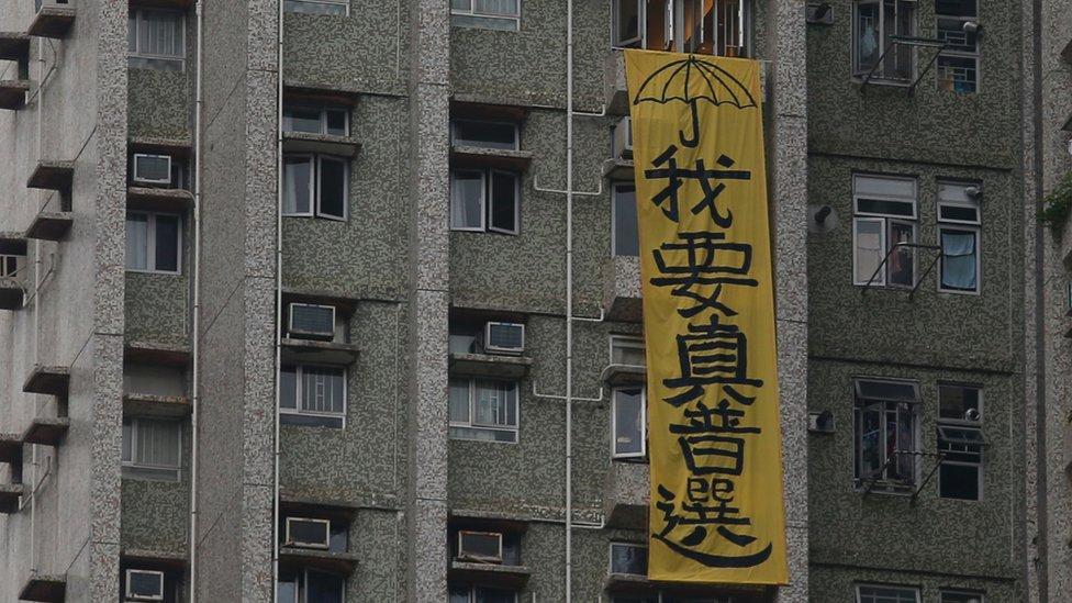 張德江訪港時,他參訪地點附近的居民樓外掛出抗議標語。
