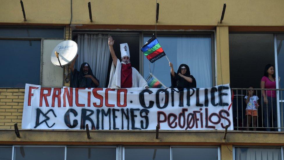 Personas con pancartas protestando contra el papa