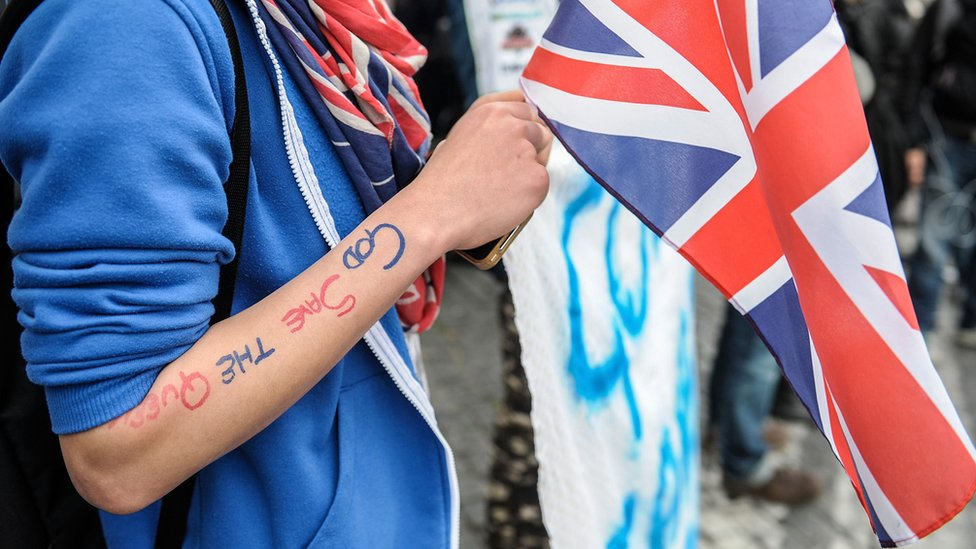 Figure wearing union jacks and holding a flag, with God Save the Queen written on their arm