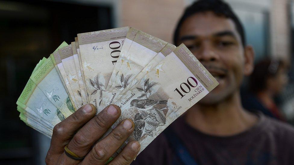 Un señor con billetes en la mano