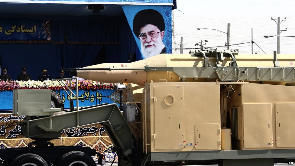A military lorry carries a Qadr medium-range missile past portraits of Iran's Supreme Leader, Ayatollah Ali Khamenei, at a parade in Tehran (22 September 2014)