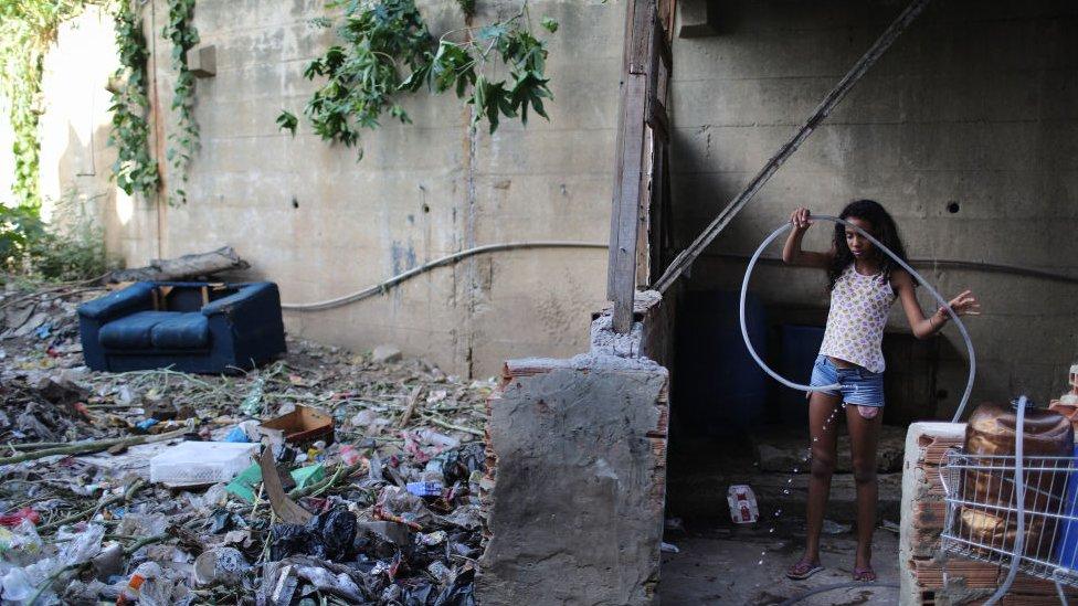 Una niña brasileña juega en un área abandonada.