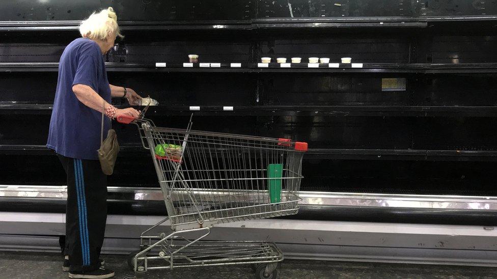 Una señora en un supermercado ante una cámara vacía.
