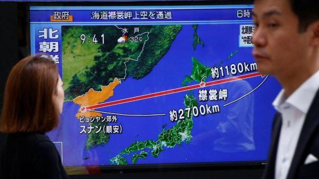 Pessoas olham uma TV que traz notici�rio em japon�s sobre o m�ssil norte-coreano