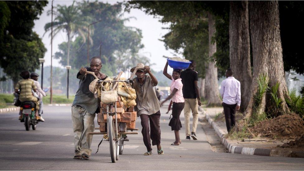 Hombres empujando bicicletas cargadas al máximo en las calles de Kananga