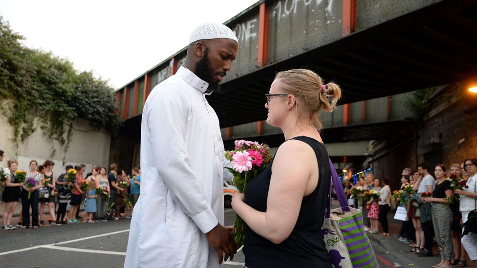 Joven entregando una flor a un joven musulmán