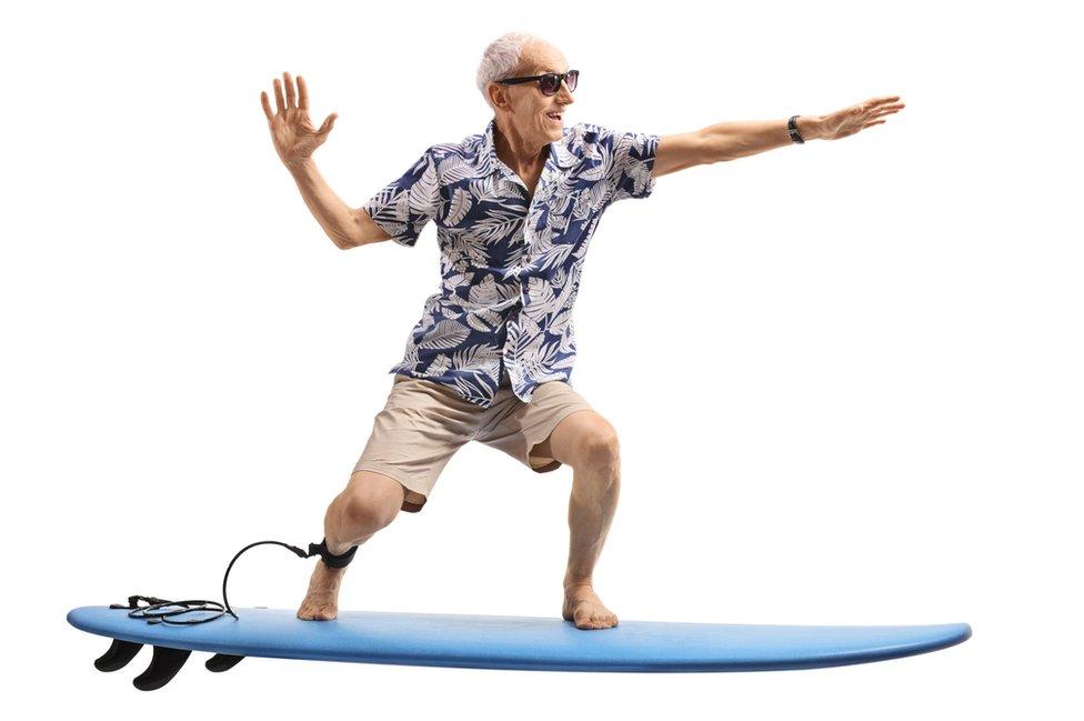 Hombre mayor simula surfear.