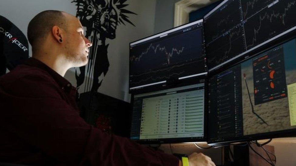 Un hombre delante de monitores de computadora