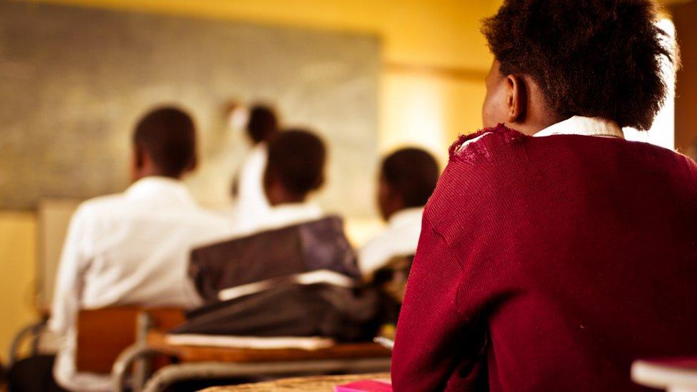 Una estudiante de espalda presta atención a la clase (imagen ilustrativa).